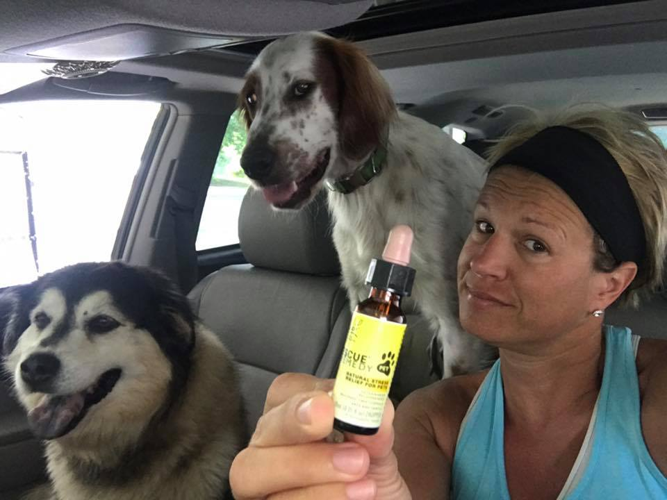 Image of two dogs and woman displaying bottle of Rescue Remedy